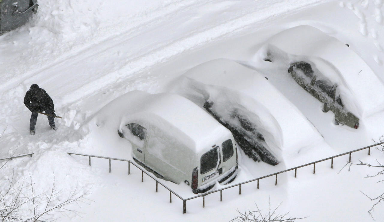 A driver shovels snow off his vehicle in Kiev, Ukraine, Saturday, March 23, 2013. Heavy snow storms from the Balkan region have been stricken Ukraine since last afternoon, in the last winter attack at the end of the first spring month. (AP Photo/Efrem Lukatsky)
