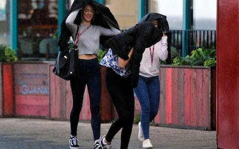 A group of girls battle against the strong winds hitting Blackpool, Lancs - Credit: SWNS