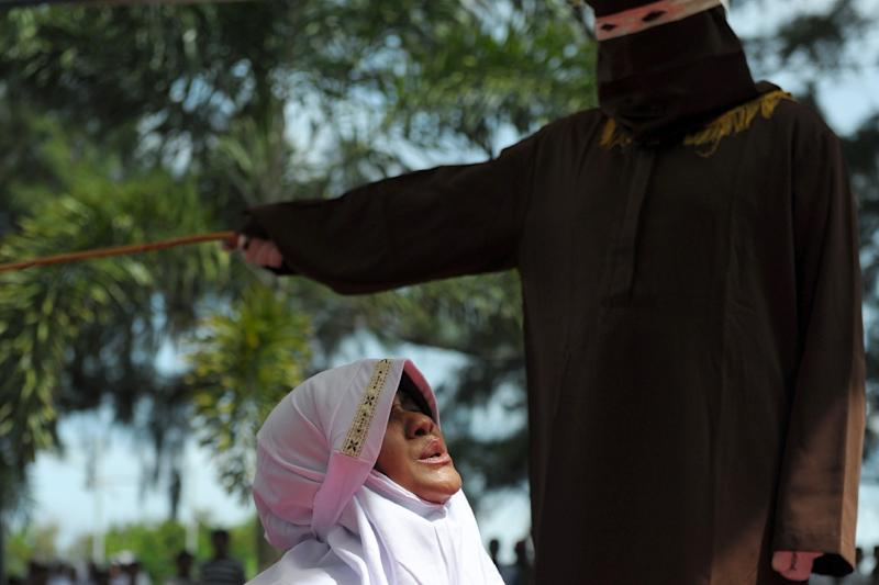 A religious officer canes a woman for spending time in close proximity with a man who is not her husband in Banda Aceh, Indonesia, on November 28, 2016