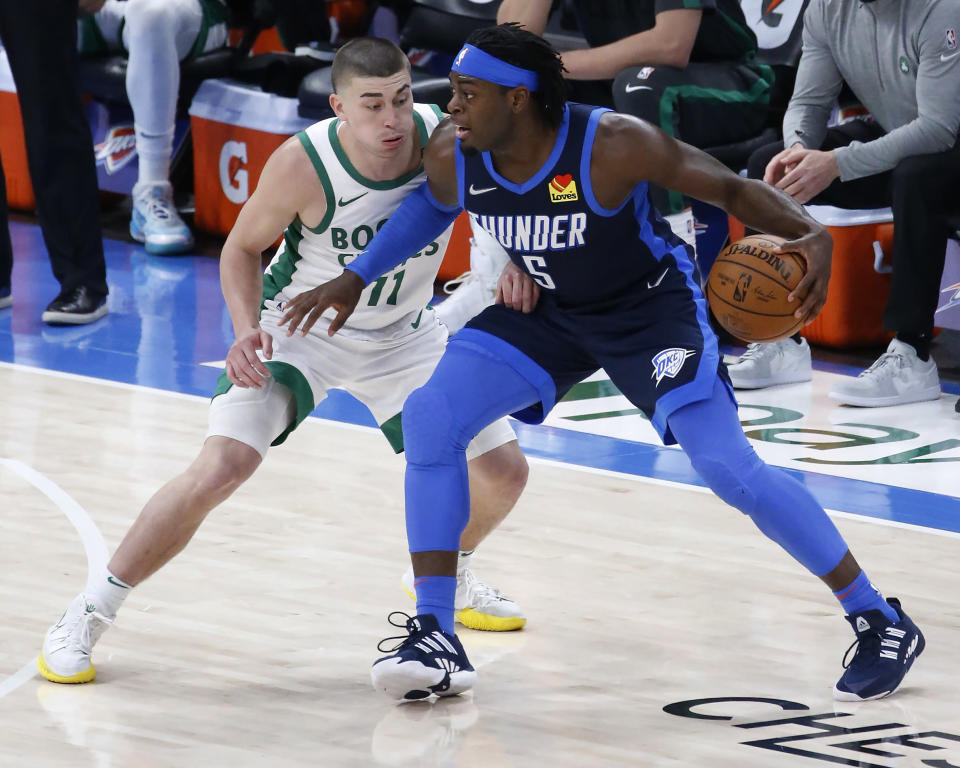 Oklahoma City Thunder forward Luguentz Dort (5) works against Boston Celtics guard Payton Pritchard (11) during the first half of an NBA basketball game Saturday, March 27, 2021, in Oklahoma City. (AP Photo/Garett Fisbeck)