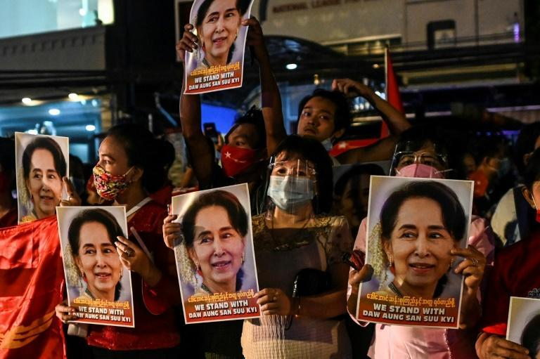 Supporters of Myanmar's National League for Democracy (NLD) hold posters with the image of Nobel laureate Aung San Suu Kyi, the country's civilian leader, as they celebrate what they say is a landslide victory in elections