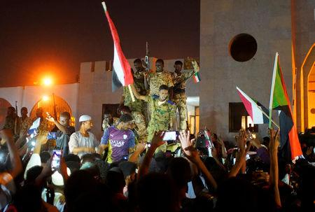 Sudanese military join demonstrators to celebrate after the Defence Minister Awad Ibn Auf stepped down as head of the country's transitional ruling military council, as protesters demanded quicker political change, outside the Defence Ministry in Khartoum, Sudan April 13, 2019. REUTERS/Stringer