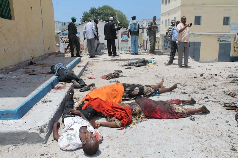 Bodies lay in the street outside a restaurant in Mogadishu, Somalia, Saturday, Sept, 7, 2013. Police in Somalia say two explosions against a restaurant frequented by government workers has killed at least 15 people. Early reports indicated that a car bomb blast and a suicide bomber attacked a restaurant near Mogadishu's State House. The restaurant, The Village, has been attacked by militants before. (Farah Abdi Warsameh)