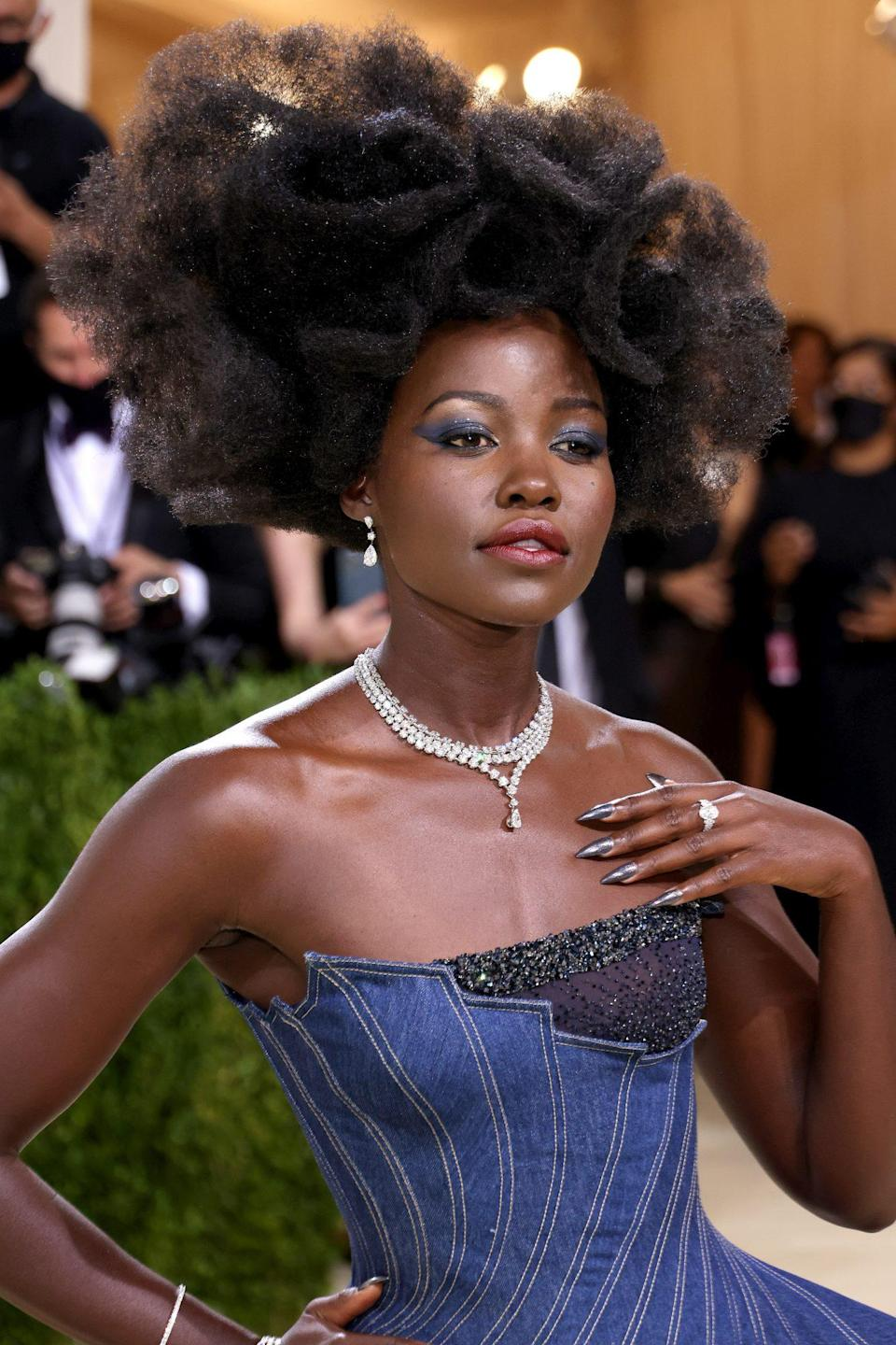 """<p>When it comes to Lupita Nyong'o, makeup artist <a href=""""https://www.instagram.com/nickbarose/"""" rel=""""nofollow noopener"""" target=""""_blank"""" data-ylk=""""slk:Nick Barose"""" class=""""link rapid-noclick-resp"""">Nick Barose</a> does <em>not </em>play around. He used Lancôme's Hypnôse 5-Color Eyeshadow Palette to match the star's eyes to her denim gown — a perfect ode to American fashion. For hair, Vernon François crafted a gorgeous, gravity-defying, structural afro that once again proves coily hair can <em>literally </em>do anything. </p>"""