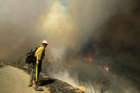 A firefighter watches as a wildfire burns Wednesday, Oct. 13, 2021, in Goleta, Calif. A wildfire raging through Southern California coastal mountains threatened ranches and rural homes and kept a major highway shut down Wednesday as the fire-scarred state faced a new round of dry winds that raise risk of flames. The Alisal Fire covered more than 22 square miles (57 square kilometers) in the Santa Ynez Mountains west of Santa Barbara. (AP Photo/Ringo H.W. Chiu)