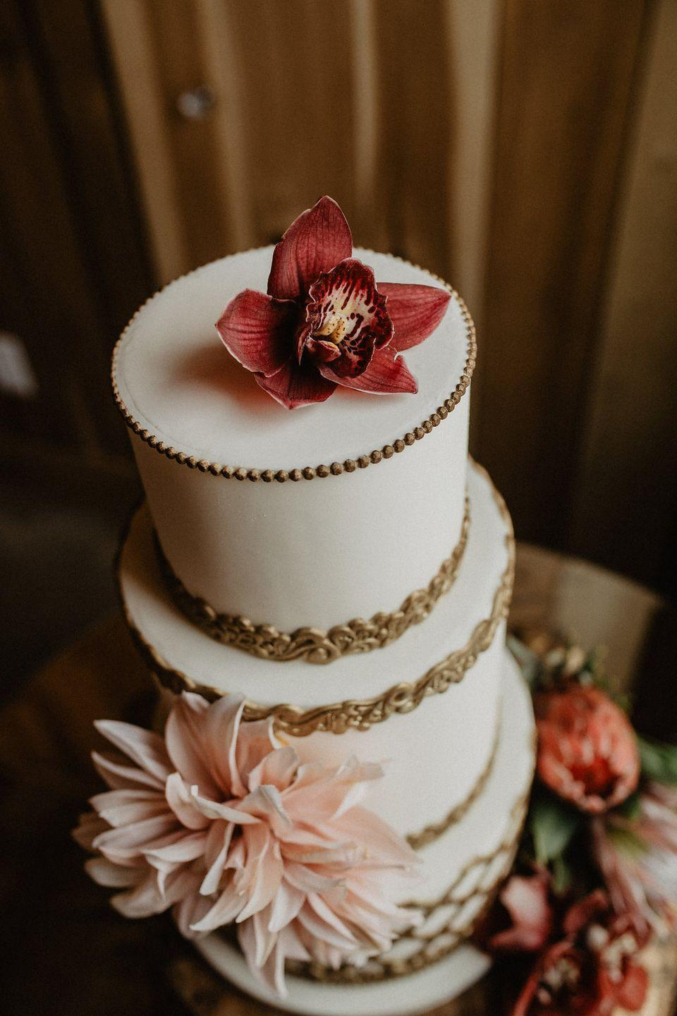 <p>Gilded edges define the tiers of Tis' So Sweet's white wedding cake for fall.<br></p>