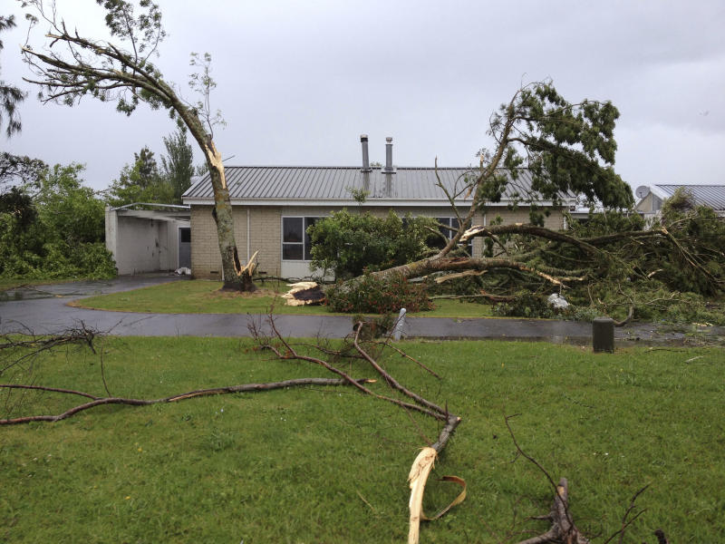 In this photo made with a mobile phone, a tree is damaged on a property in Auckland, New Zealand, following a tornado Thursday, Dec. 6, 2012. A small tornado ripped through the city, leaving at least three people dead. (AP Photo/New Zealand Herald) AUSTRALIA OUT, NEW ZEALAND OUT