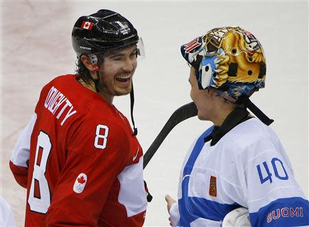 Canada's Doughty laughs with Finland's goalie Rask after Canada defeated Finland in overtime in their men's preliminary round ice hockey game at the 2014 Sochi Winter Olympics