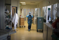 A healthcare worker wearing protective equipment walks through the intensive care unit at the Joseph Imbert Hospital Center in Arles, southern France, Wednesday, Oct. 28, 2020. Many French doctors are urging a new nationwide lockdown, noting that 58% of the country's intensive care units are now occupied by COVID patients and medical staff are under increasing strain. (AP Photo/Daniel Cole)
