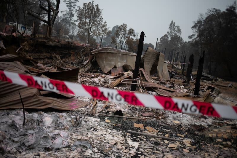 """A cordon tape with the word """"Danger"""" is seen in front of a burnt down shop in the village of Mogo"""