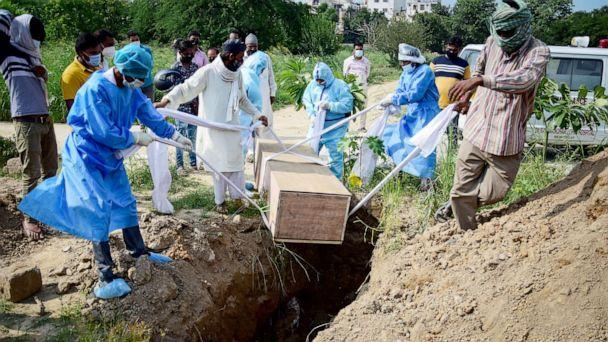 PHOTO: Relatives wearing protective suits as a precaution lower the body of a covid-19 victim for burial at a graveyard in New Nelhi, India, Sept. 3, 2020. (Manish Rajput/SOPA Images via Getty Images)
