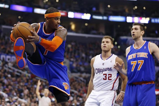 New York Knicks' Carmelo Anthony, left, pulls in a defensive rebound in front of Los Angeles Clippers' Blake Griffin, center, and Knicks' Andrea Bargnani, right, of Italy, during the first half of an NBA basketball game in Los Angeles, Wednesday, Nov. 27, 2013. (AP Photo/Danny Moloshok)