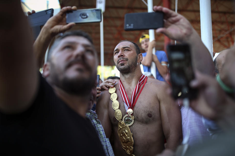 Wrestler Ali Gurbuz poses for pictures with fans after winning the final to gain the sport's golden belt in the 660th instalment of the annual Historic Kirkpinar Oil Wrestling championship, in Edirne, northwestern Turkey, Sunday, July 11, 2021.Thousands of Turkish wrestling fans flocked to the country's Greek border province to watch the championship of the sport that dates to the 14th century, after last year's contest was cancelled due to the coronavirus pandemic. The festival, one of the world's oldest wrestling events, was listed as an intangible cultural heritage event by UNESCO in 2010. (AP Photo/Emrah Gurel)