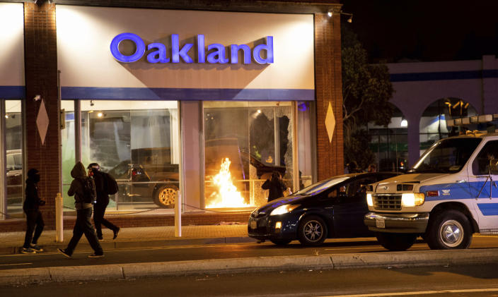 Demonstrators set fires at a Honda dealership during a protest against police brutality in Oakland, Calif., on Friday, April 16, 2021. (AP Photo/Ethan Swope)