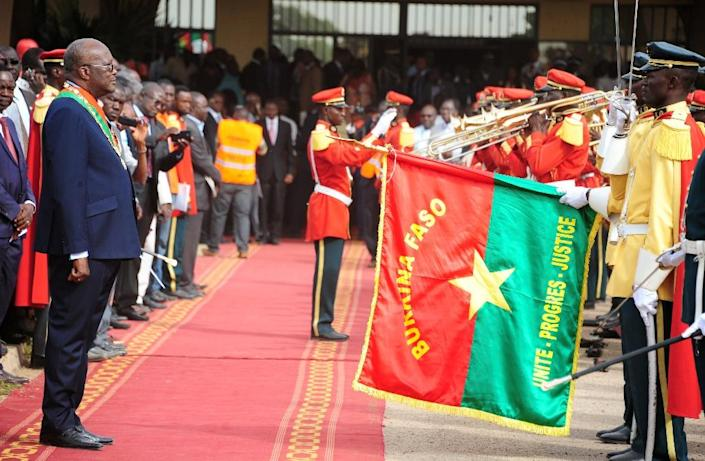Burkina Faso's new president Roch Marc Christian Kabore reviews a military honour guard following his swearing-in ceremony in Ouagadougou on December 29, 2015 (AFP Photo/Ahmed Ouoba)