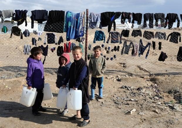 Children hold water containers in al-Hol camp, Syria, on January 8, 2020.