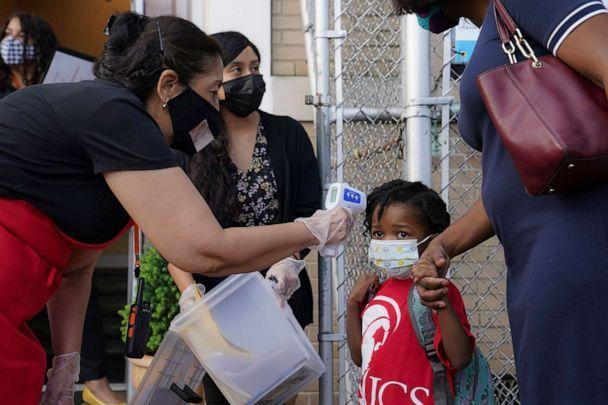 PHOTO: A student has their temperature taken as they arrive for classes while observing COVID-19 prevention protocols in the Bronx borough of New York, Sept. 9, 2020. (John Minchillo/AP)