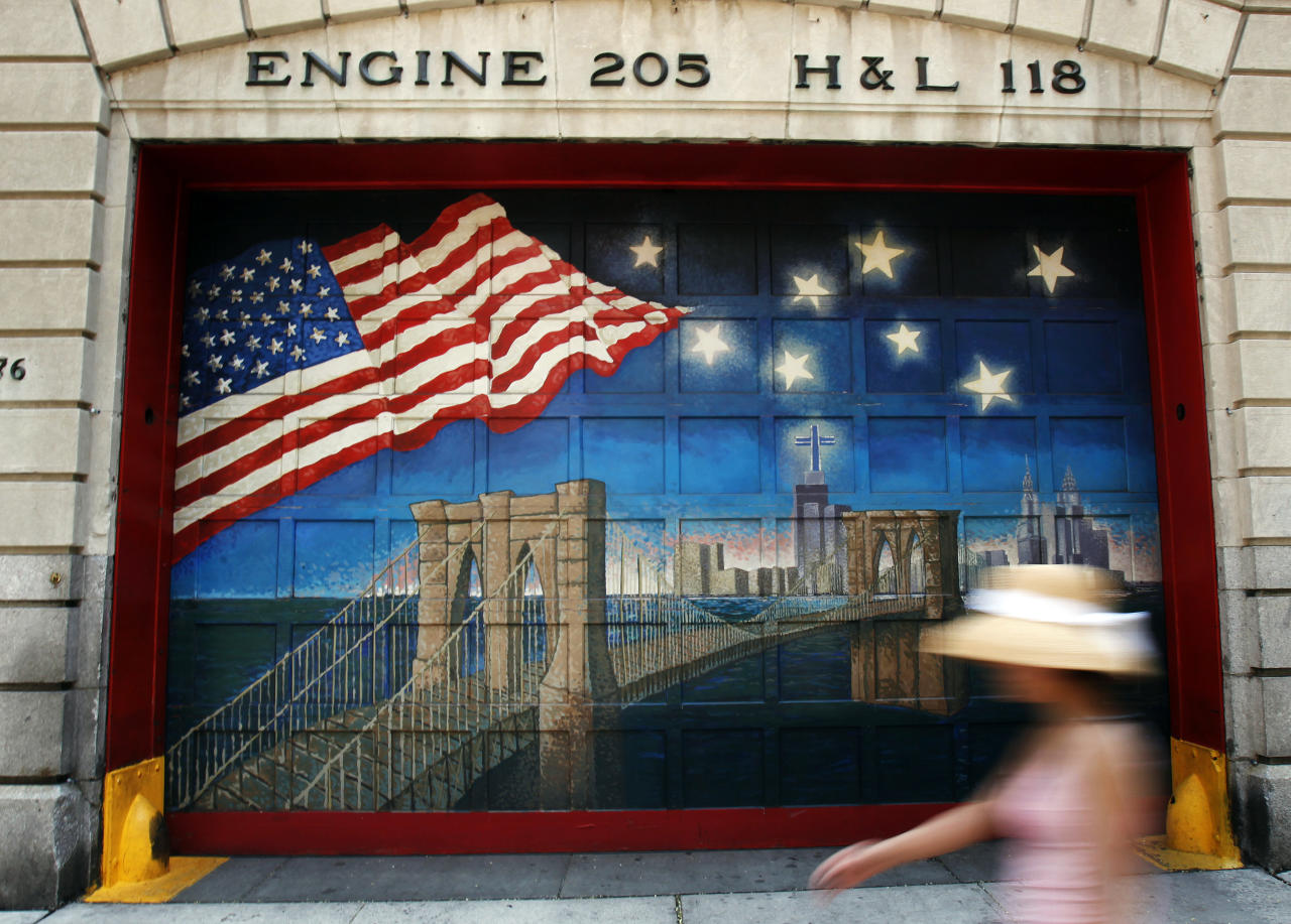 A woman walks by a mural honoring victims of the September 11, 2001 attacks on the World Trade Center outside the FDNY Engine Company 205 and Hook & Ladder Company 118 firehouse in the Brooklyn borough of New York August 2, 2011. (REUTERS/Shannon Stapleton)