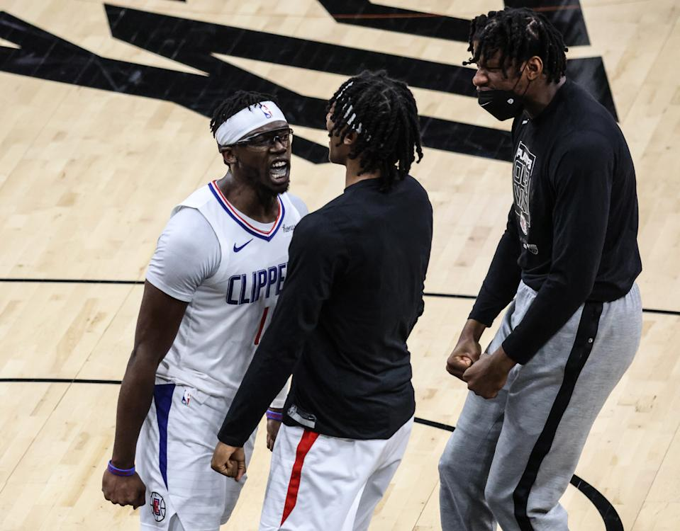 Clippers guard Reggie Jackson (1) celebrates with teammates Terance Mann and Daniel Oturu, right, late in a Game 5 win. (Robert Gauthier/Los Angeles Times via Getty Images)