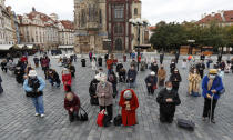 Dozens of worshippers pray during a mass celebrated at Old Town Square in Prague, Czech Republic, Sunday, Oct. 18, 2020. As Czech Republic battles new spike of coronavirus infections newly adopted COVID-19 restrictive measures limit indoor gatherings to six people or less. (AP Photo/Petr David Josek)