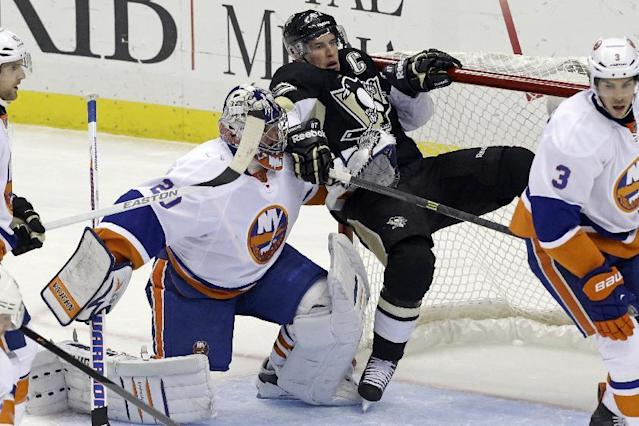 Pittsburgh Penguins' Sidney Crosby, second from right, collides with New York Islanders goalie Evgeni Nabokov (20) in the first period of an NHL hockey game in Pittsburgh, Friday, Oct. 25, 2013. (AP Photo/Gene J. Puskar)