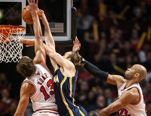 Chicago Bulls' Joakim Noah blocks a shot by the Indiana Pacers' Lou Admundson and is called for a foul during the first quarter of an NBA basketball game in Chicago on Monday, March 5, 2012. Bulls' Taj Gibson is at right. (AP Photo/Charles Cherney)