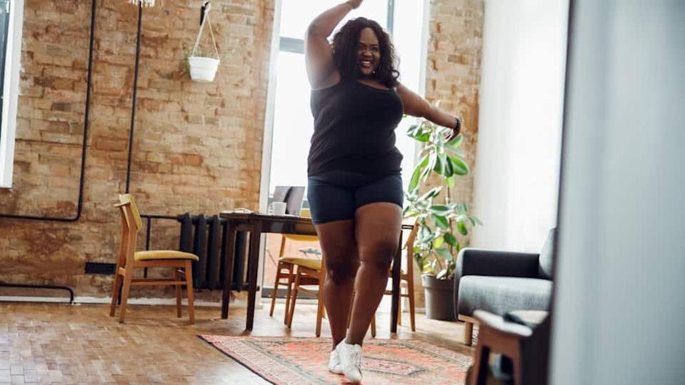 Happy woman with excess weight smiling and dancing alone in sports clothes