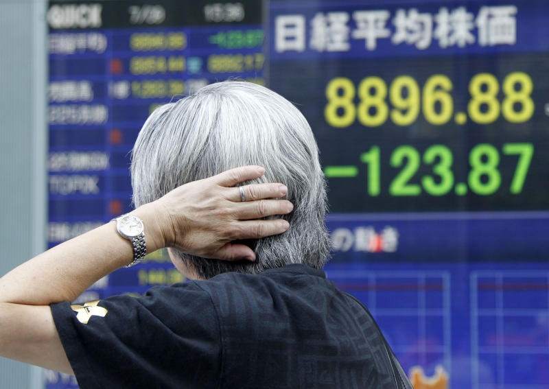 A man looks at a stock index display of a securities firm in Tokyo Monday, July 9, 2012. Asian stocks were lower Monday after a disappointing U.S. jobs report stoked concern that the world's biggest economy remains mired in weak growth. (AP Photo/Koji Sasahara)