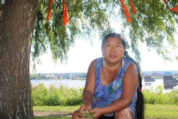 Cecelia Brooks of St. Mary's First Nation says climate change is threatening traditional plants and medicines. The orange ribbons above Brooks are tied to a willow tree to honour the memory of schoolchildren whose unmarked graves were found on former residential school grounds.  (Oscar Baker - image credit)