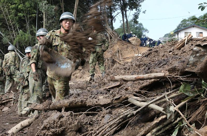 Rescue workers search for victims in the mud on August 23, 2014, three days after a landslide hit a residential area in Hiroshima, western Japan (AFP Photo/Jiji Press)