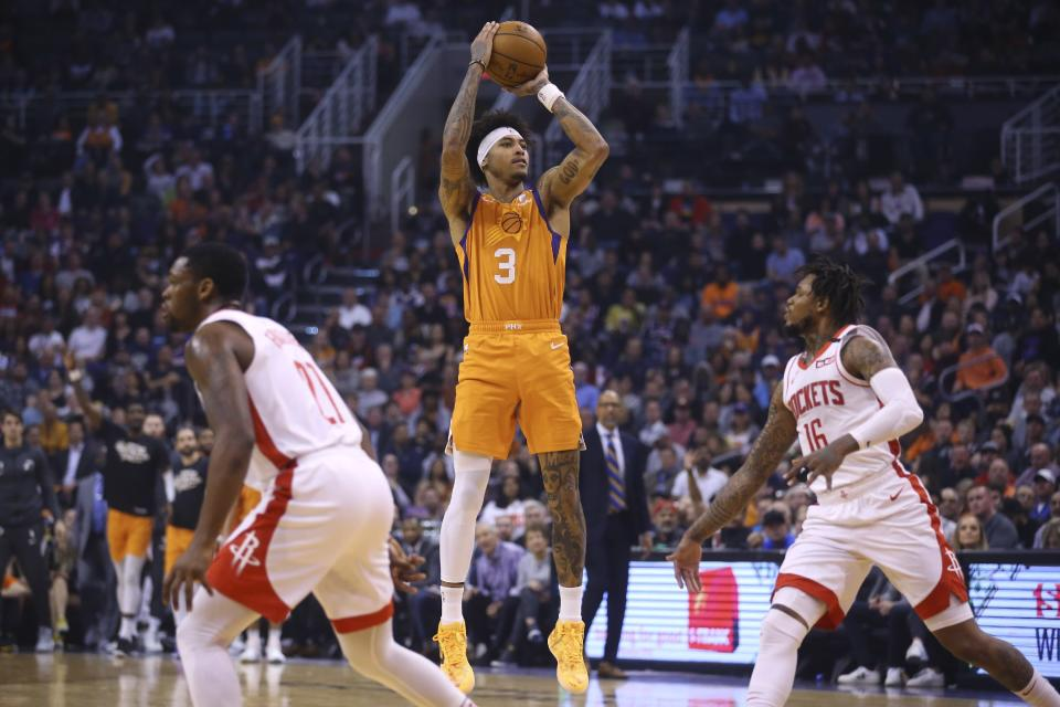 Phoenix Suns forward Kelly Oubre Jr. (3) shoots a three-point basket between Houston Rockets guards Ben McLemore (16) and Michael Frazier (21) during the second half of an NBA basketball game Friday, Feb. 7, 2020, in Phoenix. (AP Photo/Ross D. Franklin)