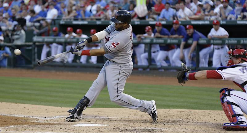 Cleveland Indians Carlos Santana, left, hits a three run RBI double in front of Texas Rangers catcher A.J. Pierzynski during the third inning of a baseball game Monday, June 10, 2013, in Arlington, Texas. (AP Photo/LM Otero)