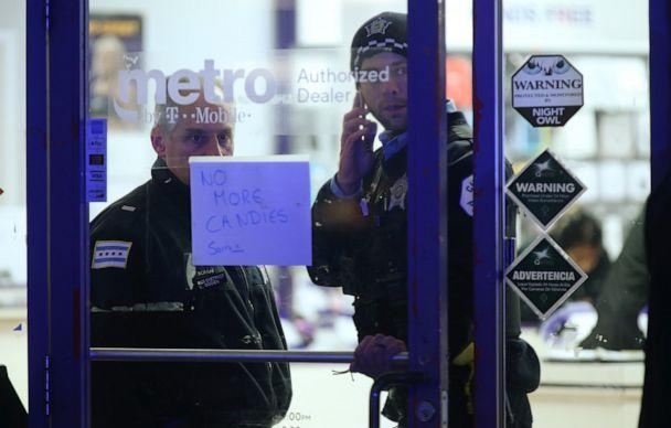 PHOTO: A police supervisor and officer stand inside a cellphone store in the 3700 block of West 26th Street in Chicago, where a 7-year-old girl who was shot while trick-or-treating was brought inside until transported, on Thursday, Oct. 31, 2019. (John J. Kim/Chicago Tribune/Tribune News Service via Getty Images)