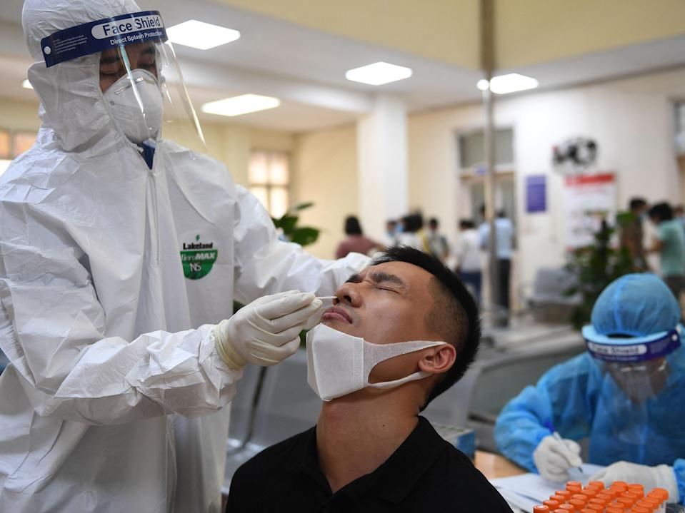<p>A health worker conducts a Covid-19 test on a man at Hanoi's Center for Disease Control and Prevention on 22 May</p> (Nhac NGUYEN/AFP via Getty Images)