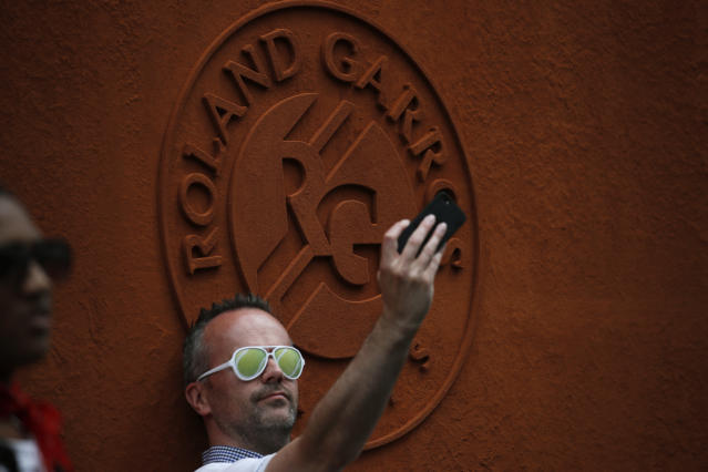 A tennis fan takes a selfie with the Roland Garros logo during first round matches of the French Open tennis tournament at the Roland Garros stadium in Paris, Sunday, May 26, 2019. (AP Photo/Christophe Ena )