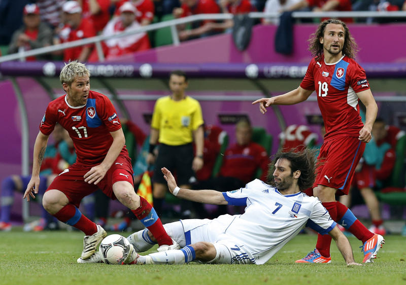 Greece's Giorgos Samaras tackles Czech Republic's Tomas Hubschman during the Euro 2012 soccer championship Group A match between Greece and Czech Republic in Wroclaw, Poland, Tuesday, June 12, 2012. (On the right is Czech Republic's Petr Jiracek. (AP Photo/Antonio Calanni)