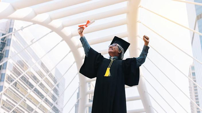 Happy senior adult man in a hat  with his gown on graduation day.