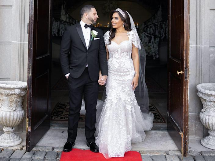 Vishnell and her husband look at each other in a doorway on their wedding day