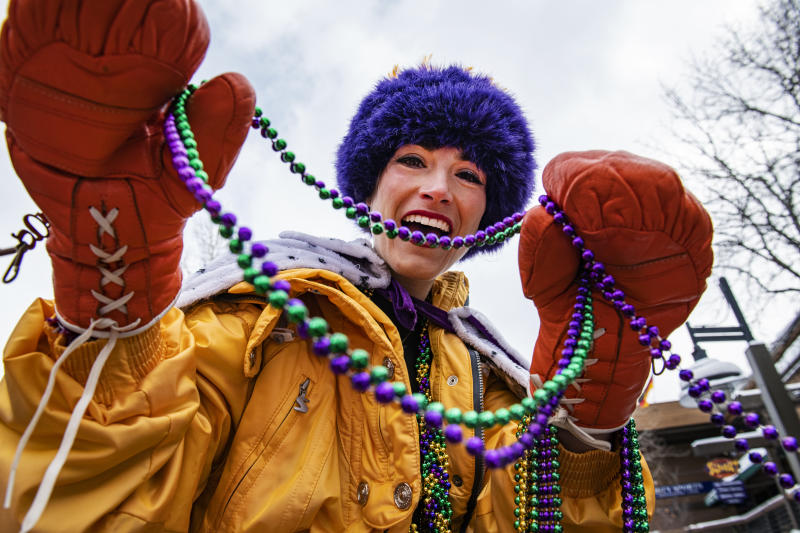 "Ariana ""Air"" Gradow places bead necklaces on passersby for the Mardi Gras celebration on Snowmass Village Mall on Tuesday, Feb. 25, 2020 in Snowmass, Colo. Gradow was born and raised in the valley and is starting circus classes at Red Brick in Aspen. (Kelsey Brunner/The Aspen Times via AP)"