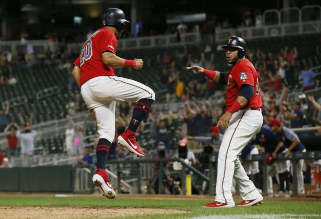 Minnesota Twins' Eddie Rosario, left, and Nelson Cruz celebrate after scoring on a two-run single by Marwin Gonzalez off Chicago White Sox pitcher Jose Ruiz to tie the score during the 12th inning of a baseball game Tuesday, Sept. 17, 2019, in Minneapolis. The Twins won 9-8 when Ronald Torreyes was hit by a Ruiz pitch with the bases loaded in the 12th. (AP Photo/Jim Mone)