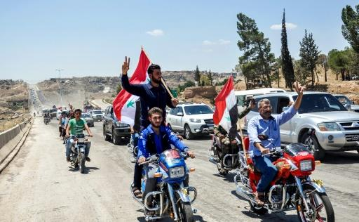 Motorcyclists carry Syrian national flags and wave as they drive along the M5 highway between Homs and Hama in the centre of the country