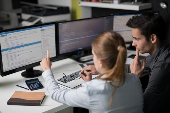 Two software engineers working together with multiple monitors displaying source code.