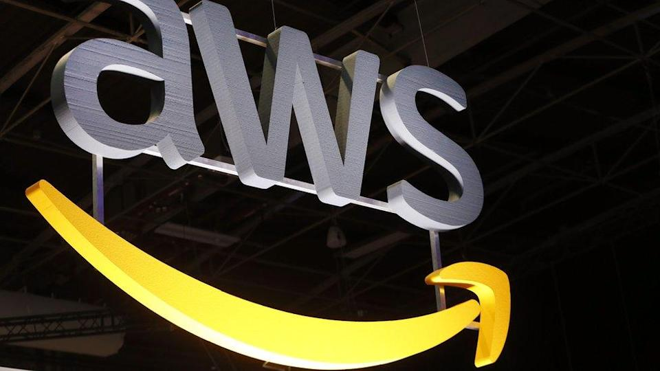 The AWS logo hangs suspended from a ceiling, lit dramatically from below