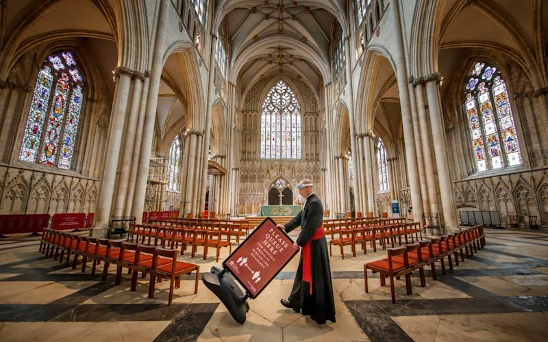 The Reverend Michael Smith, York Minster's Canon Pastor, moves a social distancing sign at York Minster, as the cathedral is preparing to welcome people back for individual prayer from Tuesday 16 June - PA/Danny Lawson