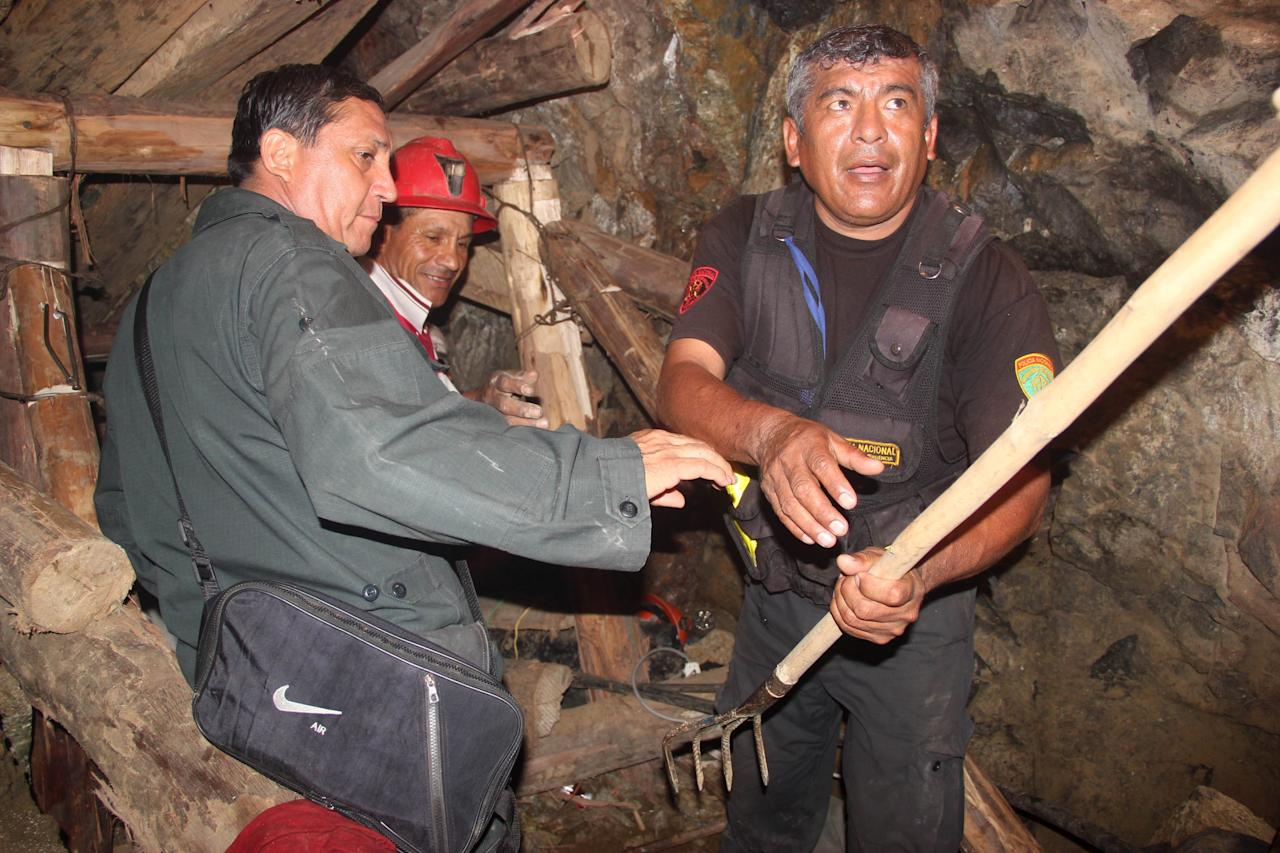 People work in a collapsed mine to rescue trapped miners in Ica, Peru, Saturday, April 7, 2012. According to Peruvians authorities, nine miners trapped since Thursday in a collapsed mine are being supplied with sports drinks, soup and food while police, firefighters and other workers work to free them. (AP Photo) PERU OUT - NO PUBLICAR EN PERU