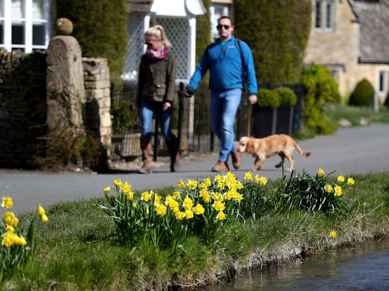 Dog walkers enjoy the sunshine Lower Slaughter, Cotswolds, Gloucestershire, 29 March 2020: David Davies/PA