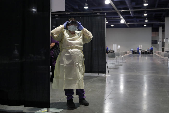 FILE - In this May 21, 2020 file photo a nurse dons personal protective equipment before the opening of a temporary coronavirus testing facility for casino employees at the Las Vegas Convention Center, in Las Vegas. Health officials in Las Vegas say they hope to administer more than 1,000 doses of coronavirus vaccine a day to area residents once a big drive-thru COVID-19 shot clinic opens Tuesday, May 4, 2021, at the Las Vegas Convention Center. (AP Photo/John Locher,File)