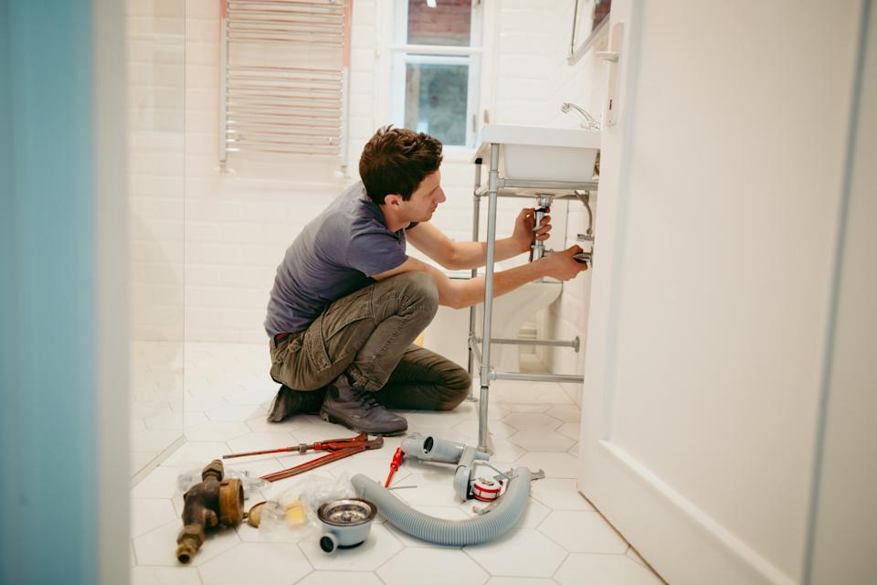 Young man fixing a leak under the bathroom sink