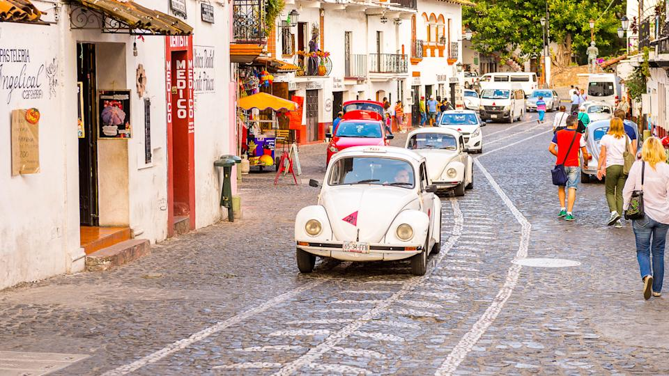 2016: White Taxi car on the street of Taxco, How Much to Tip When Traveling to These 25 Countries, MEXICO - OCT 28, Mexico. The town is known because of its Silver products, TAXCO