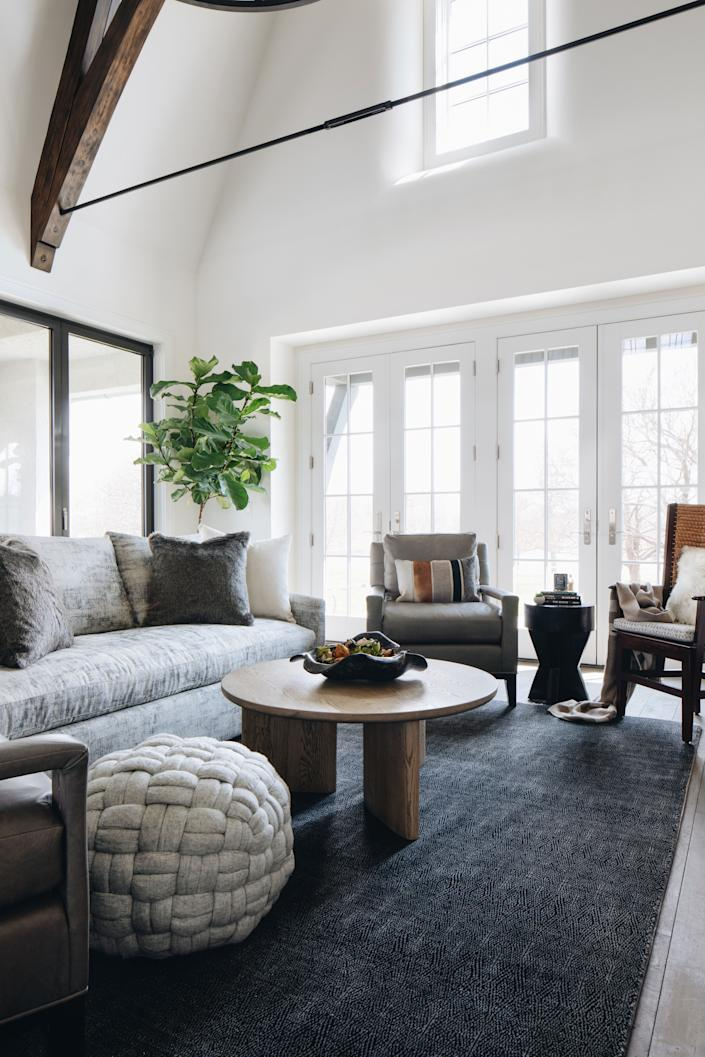 """<div class=""""caption""""> Benjamin Moore's White Heron brightens up the living room, where a <a href=""""https://bernhardt.com/"""" rel=""""nofollow noopener"""" target=""""_blank"""" data-ylk=""""slk:Bernhardt"""" class=""""link rapid-noclick-resp"""">Bernhardt</a> sofa mingles with <a href=""""https://www.stanfordfurniture.com/"""" rel=""""nofollow noopener"""" target=""""_blank"""" data-ylk=""""slk:Stanford"""" class=""""link rapid-noclick-resp"""">Stanford</a> leather chairs and an <a href=""""https://www.interludehome.com/"""" rel=""""nofollow noopener"""" target=""""_blank"""" data-ylk=""""slk:Interlude"""" class=""""link rapid-noclick-resp"""">Interlude</a> coffee table. The rug is from <a href=""""https://usa.armadillo-co.com/"""" rel=""""nofollow noopener"""" target=""""_blank"""" data-ylk=""""slk:Armadillo & Co"""" class=""""link rapid-noclick-resp"""">Armadillo & Co</a>. </div>"""